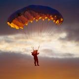 Parachutiste sur le parachute coloré en Sunny Sky Image stock