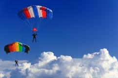 2 parachutists витают на красочных парашютах через неоглядное голубое небо на фоне белых пушистых облаков Стоковая Фотография RF