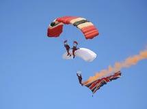 Parachutists, die eine Flagge skydiving und geschleppt worden sein würden Stockbilder