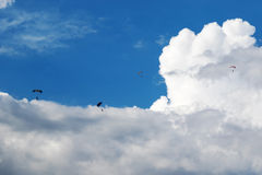 Parachutists are flying in the cloudy sky royalty free stock photos