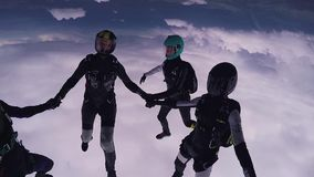 Parachutists holding hands in sky. Skydiving. Flight above green fields. Extreme sport stock video footage