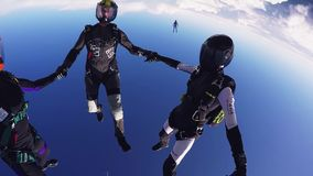 Parachutists holding hands in sky. Skydiving. Flight in blue sky. Teamwork. Extreme sport stock video
