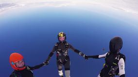 Parachutists jump from airplane, make formation in sky. Holding hands. Skydiving. Extreme sport stock video