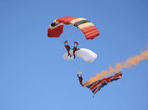 Parachutists skydiving and trailing a flag Stock Images