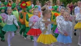 A parada da festividade, multidão de crianças em trajes diferentes anda ao longo dos cantos da rua e do grito da cidade fora vídeos de arquivo