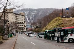 Parada de autobús turístico cerca del valle del infierno de Jigokudani con el hotel y de la montaña en fondo en Hokkaido, Japón fotografía de archivo