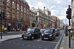 Parada del taxi para los semáforos Foto de archivo libre de regalías