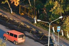 Parada do ônibus entre as árvores do outono Fotografia de Stock Royalty Free