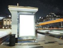 Parada do ônibus na noite da cidade com o cartaz iluminado branco da placa foto de stock