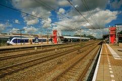 Parada locomotiva na plataforma do estação de caminhos-de-ferro, nos trilhos da estrada de ferro e no céu nebuloso azul em Weesp fotografia de stock royalty free