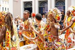 A parada pequena do dançarino com trajes tradicionais e os instrumentos que comemoram com foliões o carnaval, Brasil fotografia de stock