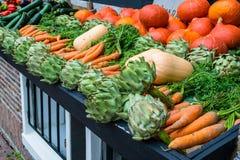 Parada vegetal con las alcachofas y las zanahorias fotografía de archivo libre de regalías