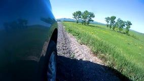 Paradas del coche en un borde de la carretera de una carretera en campo en un día de verano soleado La cámara se monta en un lado metrajes
