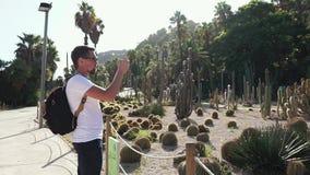 Paradas do indivíduo para tomar imagens no parque botânico filme