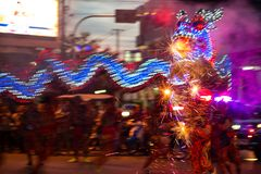 Parade of motion blurred dragon decorated by LED lights dances w royalty free stock photography