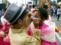 Parade participants apply make up to each other during the Sumaka Festival in Antipolo City. ANTIPOLO CITY, PHILIPPINES - MAY 1, 2017: Parade participants apply royalty free stock images