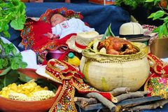 Parade Pase del Nino Viajero. Little baby sleeping surrounded by traditional ecuadorian typical food: royalty free stock images