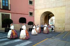 A parade in a row of women dressed whith traditional colorful clothes and dresses near. Elche, Alicante, Spain; on February 3, 2019: A parade in a row of women stock images