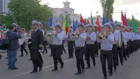 Parade of sailors, young men dressed in uniform play musical instruments and carry in hand flags of different colors stock video footage