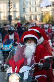 The parade of Santa Clauses on motorcycles Stock Photos