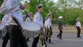 Parade at the street, sailors in uniform play on musical instruments during the march carry colorful flags stock video footage
