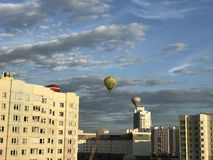 Parade van ballons over de stad Aerostaten van verschillende kleurenvlieg in de blauwe hemel boven de huizen Stock Afbeelding