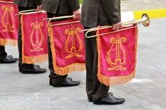 Parade van militaire muzikale het instrumententrompet van de orkestholding met rode vlag en gouden lier stock afbeelding