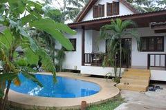 Paradijshuis met een zwembad in de keerkringen Stock Afbeeldingen