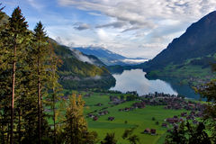 Paradise. Lake, meadows and a village in Switzerland mountains Stock Photography