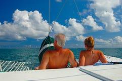 Paradise. Couple sunbath on a sail boat stock photography