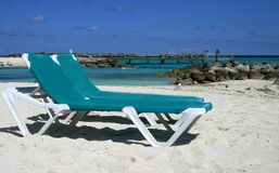 Paradise. Two lounge chairs on island beach with dock in background Stock Photography
