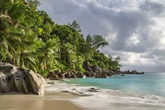 Paradise beach at anse georgette, praslin, seychelles 25. An approaching thunderstorm over the paradise. the sun shines bright under the black clouds and royalty free stock photography