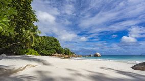 Paradise beach at anse lazio on the seychelles 74. Turquoise water, granite rocks and palm trees in the white sand on the paradise beach at anse lazio on the Royalty Free Stock Photo