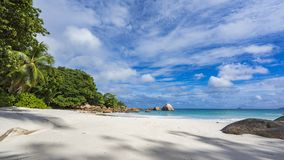 Paradise beach at anse lazio on the seychelles 81. Turquoise water, granite rocks and palm trees in the white sand on the paradise beach at anse lazio on the Stock Image