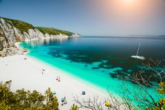 Paradise beach with clear azure emerald sea water surrounded by high white rocky cliffs. Fteri beach in Kefalonia Island stock photography
