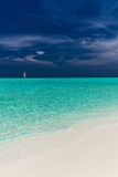 Paradise beach in Maldives with single red sail boat. In the ocean Stock Photo