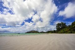 Paradise beach on the seychelles 27. Wide open paradise beach with white sand, palm trees and turquoise water on the seychelles. Simply paradise Royalty Free Stock Images
