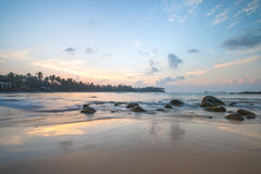 Paradise beach of Sri Lanka at sunrise. Tropical paradise beach with ocean and palm trees at sunrise in Mirissa, Sri Lanka Stock Photos