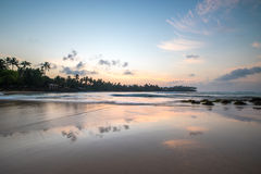 Paradise beach of Sri Lanka at sunrise. Tropical paradise beach with ocean and palm trees at sunrise in Mirissa, Sri Lanka Royalty Free Stock Photo
