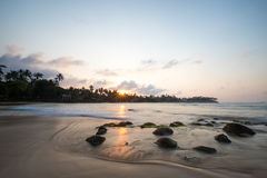 Paradise beach of Sri Lanka at sunrise. Tropical paradise beach with ocean and palm trees at sunrise in Mirissa, Sri Lanka Stock Photo
