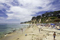 Paradise Cove Shoreline. Crowd basks in the sun and bathes in calm waters beneath a cloud-streaked sky at Paradise Cove, Malibu, California Royalty Free Stock Photography