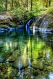 Paradise creek swimming hole with water and a short waterfall in the center on the lower Rogue River. Paradise creek swimming hole with flat clear water and a royalty free stock images