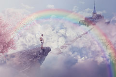 Paradise. Fantasy world imaginary view. Young boy looking at the path to a castle above clouds. Life journey below a rainbow in paradise Royalty Free Stock Image