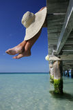 Paradise Feet and Hat. Woman with her feet over the edge of a tropical jetty Royalty Free Stock Image