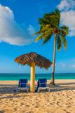 Paradise landscape. Umbrella and two lounge chairs around palm trees. Tropical beach. Caribbean sea, Holguin, Cuba, Playa Esmerald Royalty Free Stock Images