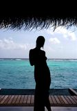 A Paradise Mirage. Silhouette of a gorgeous model with the amazing waters of the Maldives in the background Royalty Free Stock Photography