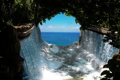 Paradise scene Blue water and blue sky seen through a waterfall and green anchor of tree branches hanging stock photography
