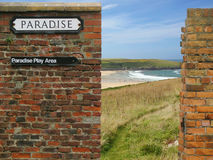 Paradise sign on old brick wall, sea/ocean beach. A PARADISE street sign on an old worn-out red brick wall, with a sea/ocean beach in the background, fence Royalty Free Stock Images