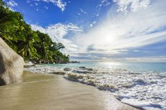 Paradise tropical beach with rocks, palm trees and turquoise wate stock photo