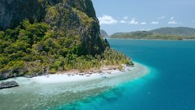 Paradise tropical sandy Ipil Beach on Pinagbuyutan island. El Nido, Palawan, Philippines. Azure turquoise ocean water. Coconut palm trees and local banca boats stock footage